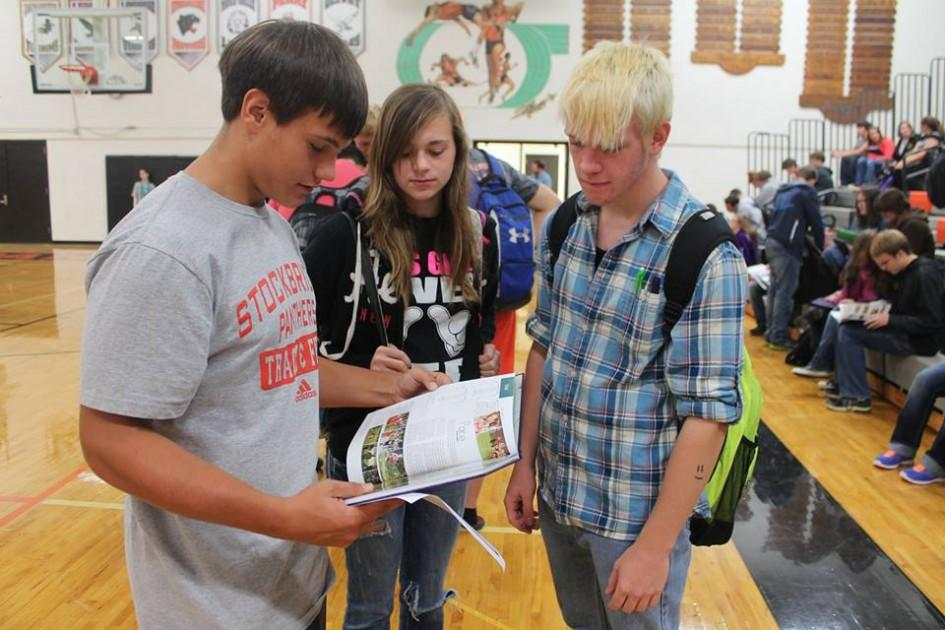 Sophomores C. Hendrickson, Z. Douglas, and G. Schniers take their first peak at The Panther yearbook at the distribution party.