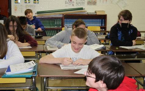 Having never been photographed by the high school news team, 8th grader Mason Beauregard shies away from the camera while studying the French and Indian war in U.S. history class.