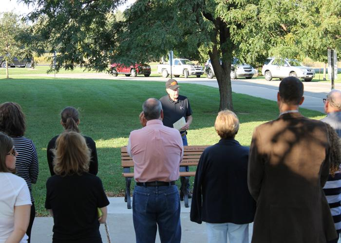Speaking to those who came to the ceremony on September 14, Merelyn Snider offers the memorial bench to the school board and shares his fond memories of his brother Darwin in front of Stockbridge High School.