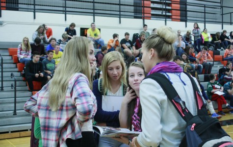 Sharing a first glimpse  of the 2015 yearbook, junior Alexis Roberts talks to  Shaylyn Sprout 11  while  sophomores Kaylee Samulak and Faith Whitt look at the