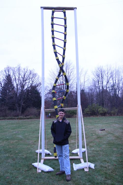 Standing in front of his masterpiece, freshman Josh Farrar shows off the structure of a DNA molecule. The 20 foot tall model cost over 200 dollars in resources to build.