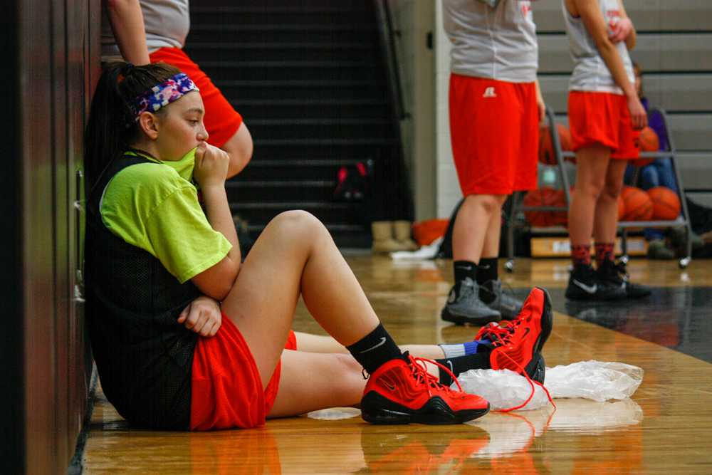 Icing her injured ankle, sophomore McKenzie Williams continues to watch the rest of the JV girls basketball team practice after she twisted her ankle by landing on someone's foot when coming down from a layup.