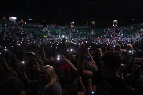 Singing along to Journey's 'Don't Stop Believing,' students wave their phone flashlights during the closing of the event. The song was picked through a poll on the Twitter page for Jostens Renaissance by the students attending.