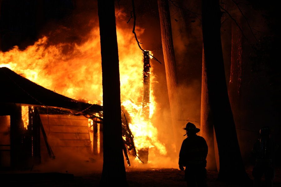 With the threat of the wind blowing the flames towards surrounding houses, a firefighter moves across the scene to analyze the backside of the burning storage building on Homewild Drive.
