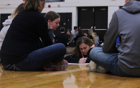 Along with the rest of her group, freshman Kelsey Andrews shares her ideas as to what she thinks helps strengthen high school students' abilities to treat people with respect as freshman Alexis Killinger writes down a list in the gym on Friday, February 10.
