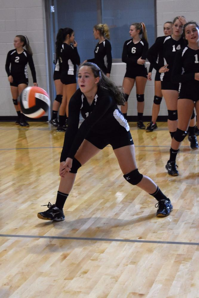 Determined, freshman Hailey Howard prepares to bump the volleyball during warm up before the first match against Olivet.