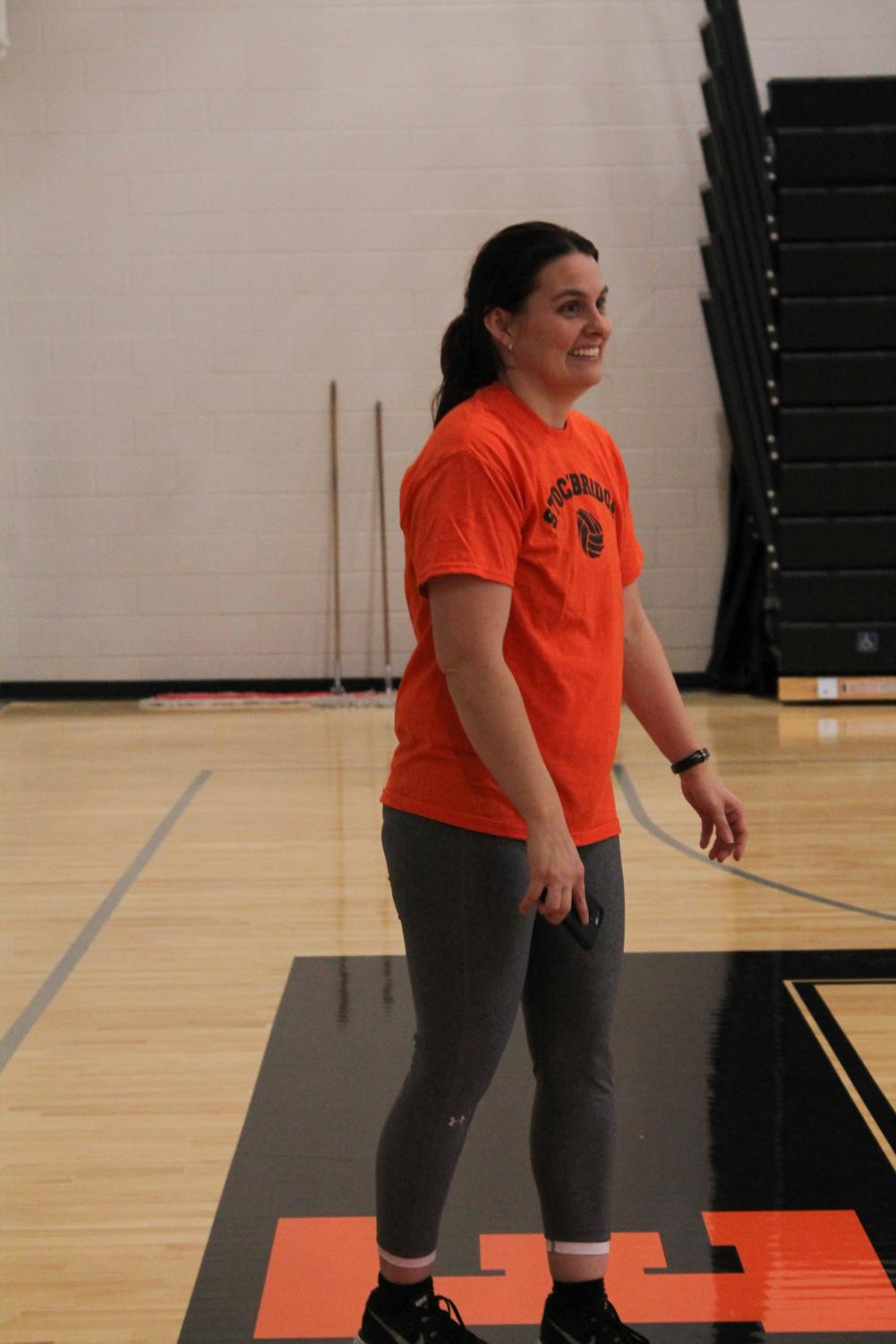 Showing her sophomore girls how to properly serve the ball, coach Villegas laughs as she watches the players learn from their unsuccessful attempts at serving the ball to their partners.