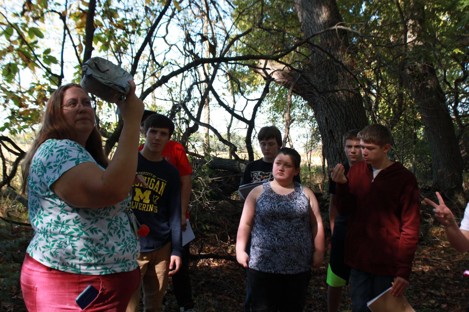 Looking into the plastic container, long-term substitute teacher Hannah Reyes describes each object's state of decay to the wildlife biology class at the outdoor nature site. The students take notes for a project in their wildlife biology class about the effects of various types of landfills. Afterward, junior Gage Place, sophomore Toby French, freshmen Clayton Allen and sophomore Morgan Payne discuss with Reyes what landfill type they believe causes the most harm to the environment.