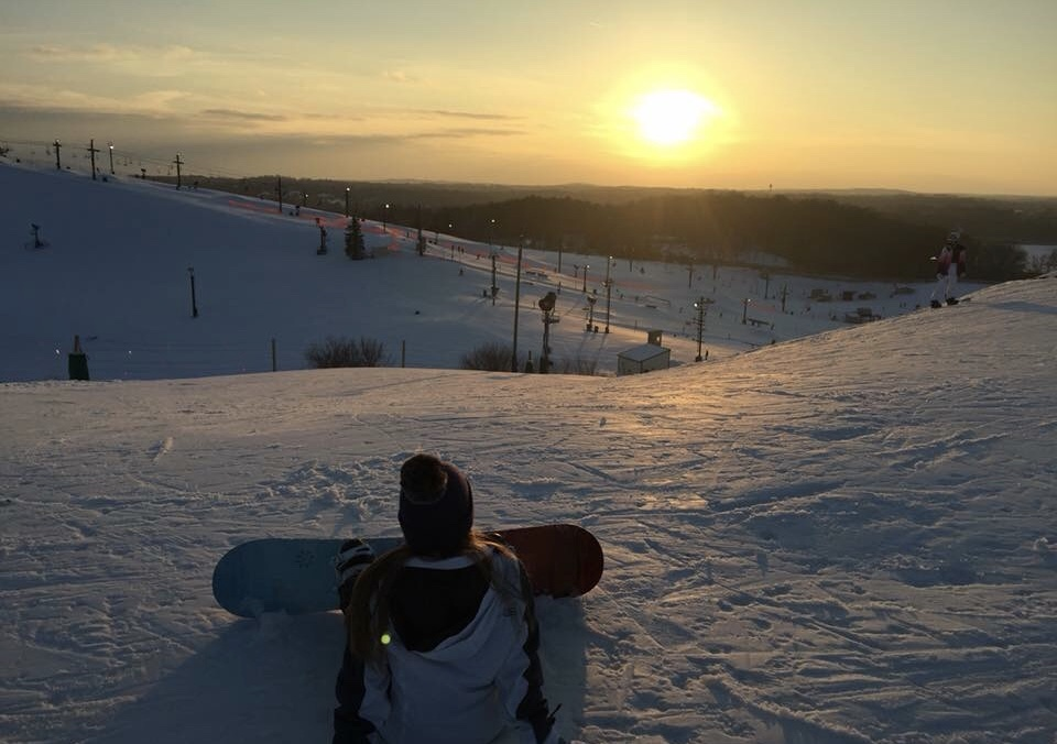 "Adjusting her snowboard bindings at the top of the Chicken Chute slope at Mt. Brighton, sophomore Rachel Owens takes in the view.  ""People should try it, even if they're not good at it,"" Owens said. ""Once you can do it, it's a lot of fun."""