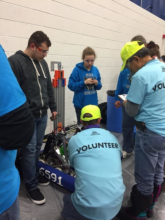 Anticipation.+Senior+Luke+Fillip+and+sophomore+Kelsey+Andrews+anxiously+wait+as+volunteers+inspect+their+robot+to+see+if+it+qualified+for+the+competition.+%E2%80%9CThere+is+a+120-page+rule+manual+that+our+robot+has+to+follow%2C%E2%80%9D+coach+Bryan+Tasior+said.%0A
