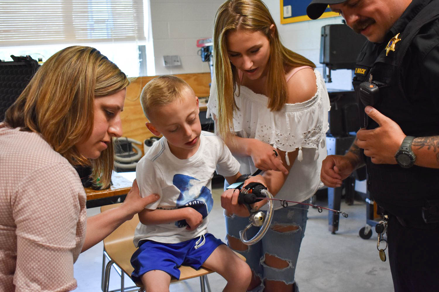 A perfect fit. Ezra's parents watch as freshman Chelsea Asquith puts the fishing rod in Ezra's hand for him to test out the feel of it. PHOTO KAITLIN MILLER.