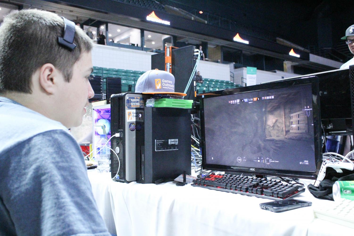 "At Eastern Michigan University, eighth grader Brenden Yannella sits in front of the monitor with extreme focus on winning the game ""Tom Clancy's Rainbow Six Siege"" as he plays as the character Sledge."