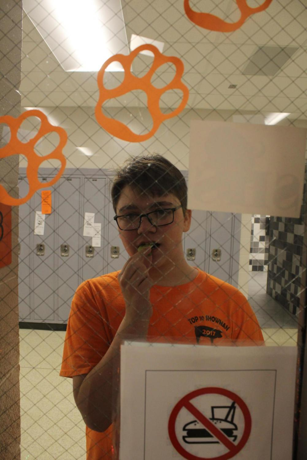In a mocking mood, sophomore Evan Williams stands outside Spanish teacher Christina Villegas' room eating a snack. Villegas, one of many instructors, allows no food in her classroom.