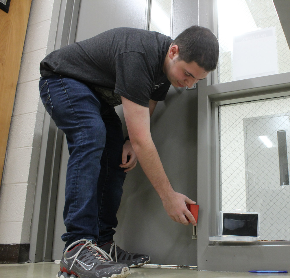 Senior Hunter Fee demonstrates how to use the new locks that were given to some teachers as a part of the school's new ALICE training. While some doors in the school open inward and can be propped with a chair, most can not.