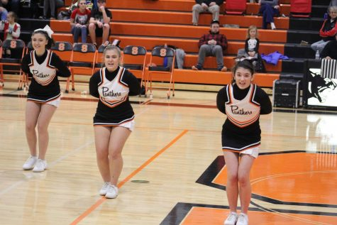 Cheering at a varsity boys home basketball game against Northwestern, sophomore Malena Rosedale and juniors Alexis Killinger and Anna Schlaff perfect their round two performance. Their coaches use games like this to get as much practice as they can get for their three-round competitions.