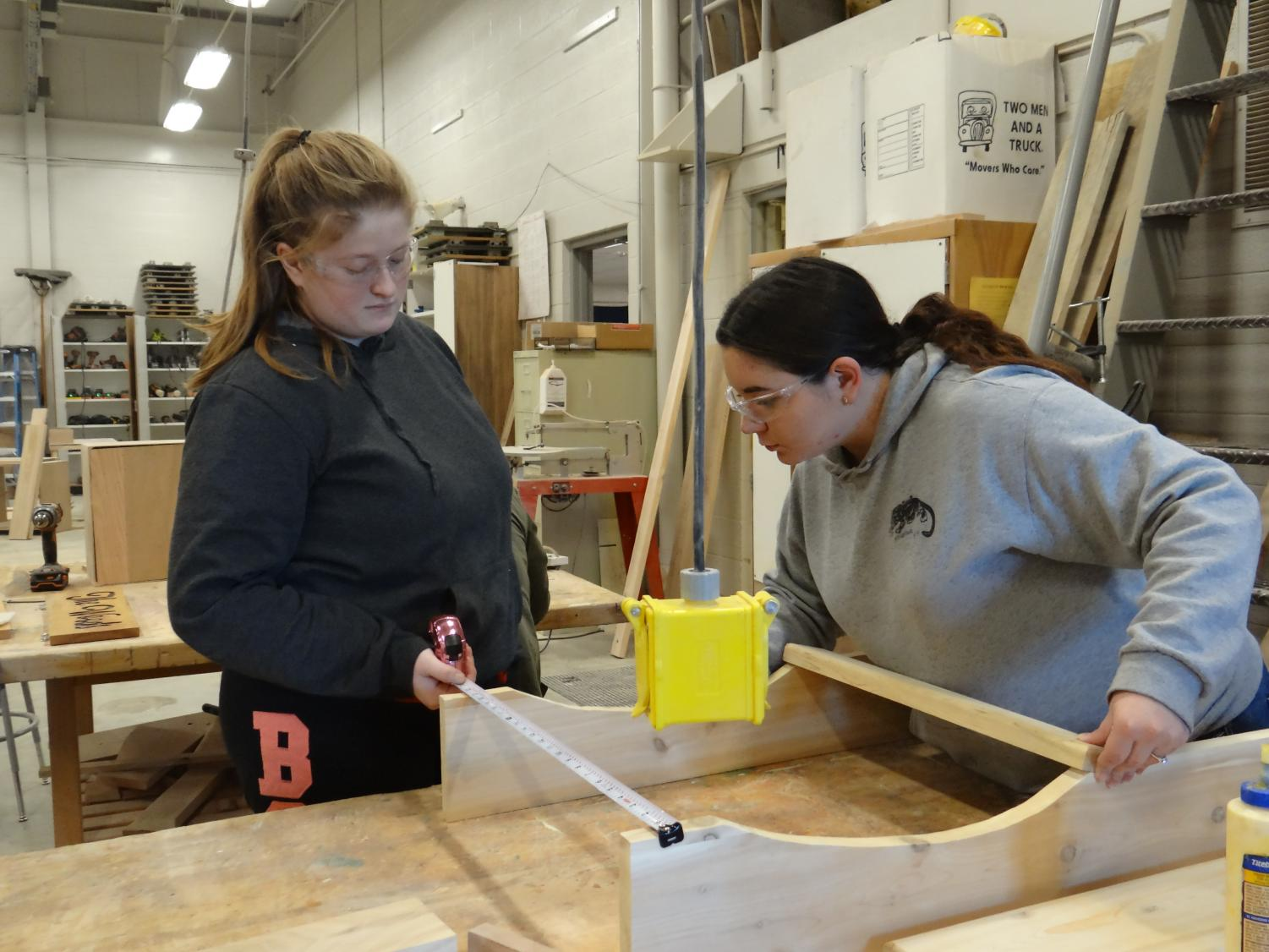 In the beginning stages of a woodworking project, senior Bethany Plennert helps senior Tayler Varner make measurements on parts of her chair, that is designed to look like the lower peninsula of Michigan
