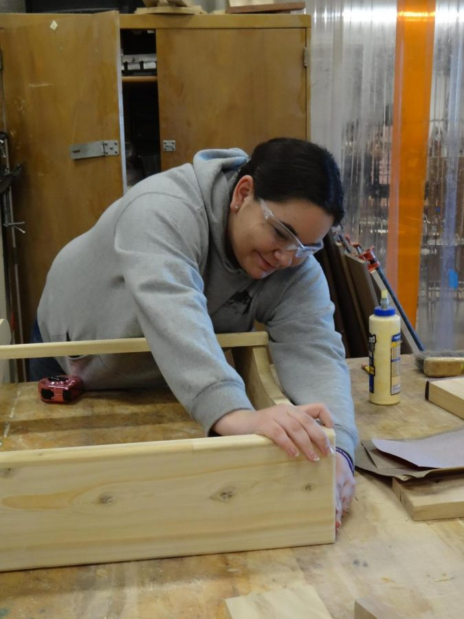 Sophomore Madison Aiken makes measurements on a board for a project, while freshman Joslynn Caskey sands her project down, getting the wood ready for oiling in woodworking. In this CTE state-funded course, students are introduced to basic woodworking skills and safety using hands-on instruction.