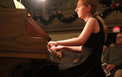 Junior performs on the piano at holiday show