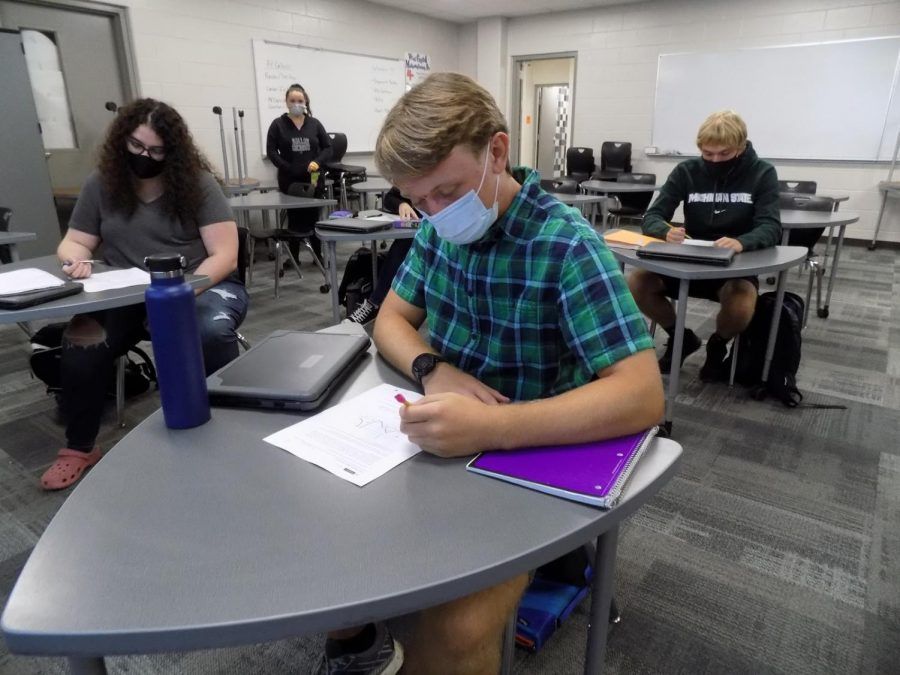 Seniors Diane Evans, Wyatt Whitaker, and Brock Jones do their work in school while socially distanced and following government protocols regarding COVID. Whitaker and his classmates follow school rules to stay properly distanced while wearing masks and keeping their hands clean often.